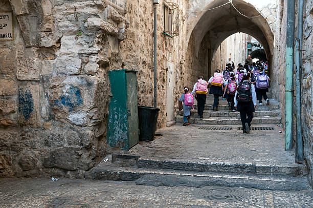Palestinian school children in East Jerusalem East Jerusalem, Occupied Palestinian Territory/Israel - October 20, 2010: Palestinian schoolchildren walk from their homes to school in the Muslim Quarter of the Old City of Jerusalem. East Jerusalem was occupied by Israel in the Six-Day War (1967) and unilaterally annexed shortly afterwards. The status of East Jerusalem is contentious, and its annexation is not legally recognized by most of the world. muslim quarter stock pictures, royalty-free photos & images