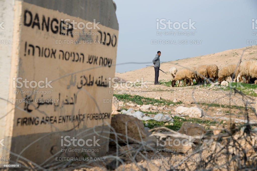 Palestinian shepherd and flock near Israeli military warning sign stock photo