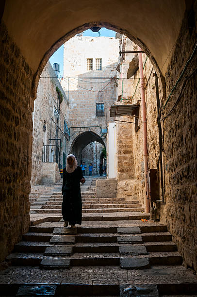Palestinians in Jerusalem's Old City Jerusalem, Israel - October 20, 2010: A Palestinian woman walks in the Muslim Quarter of the Old City. Palestinian students are also in the distance, further up the street. muslim quarter stock pictures, royalty-free photos & images