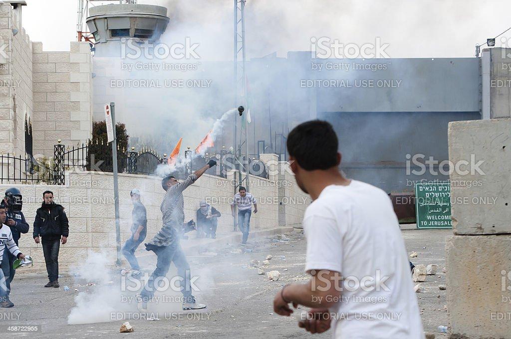 Palestinians throw back Israeli tear gas royalty-free stock photo