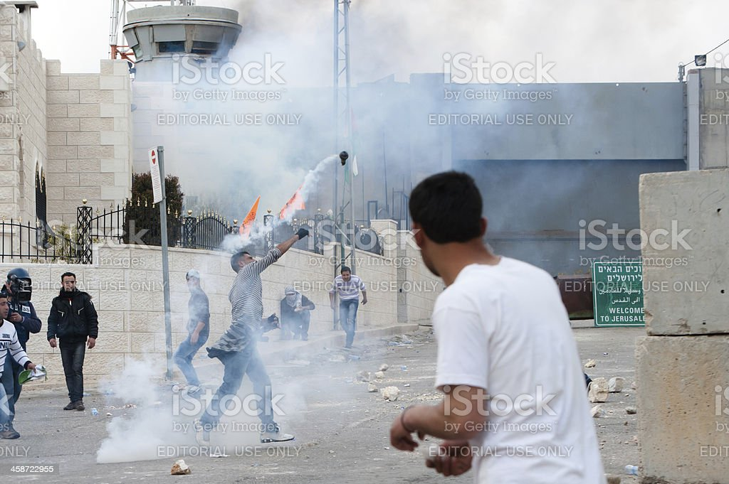 Palestinians throw back Israeli tear gas stock photo