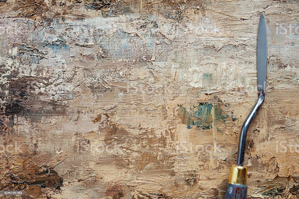 palette knife on canvas with coating of brown oil paint stock photo