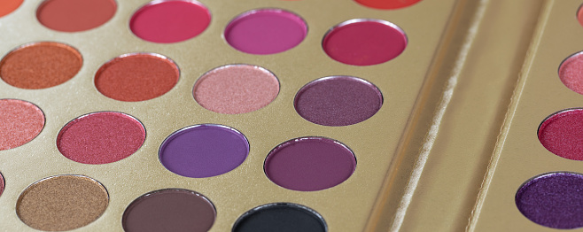 Palette of dry pressed eyeshadows in neutral tones, banner. Round refills of purple, pink, crimson shades. Beauty concept, products for make-up, visage, mineral cosmetics.