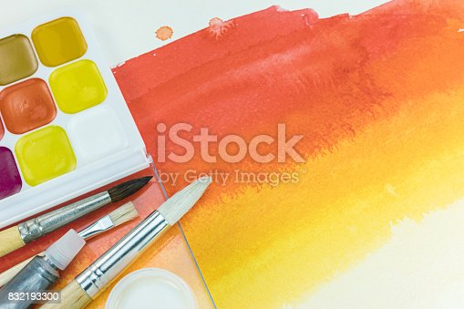 istock palette of paints and various paintbrushes on red yellow watercolor background 832193300