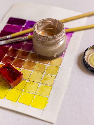 Palette with different paints and brushes on a white background