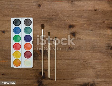 istock palette with paint and brushes on the wooden background 466024122