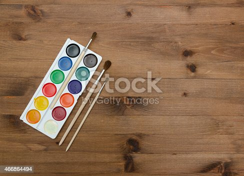 istock palette with paint and brushes on the wooden table 466864494