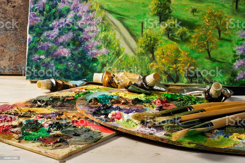 palette with paintbrushes and canvas  paintings stock photo