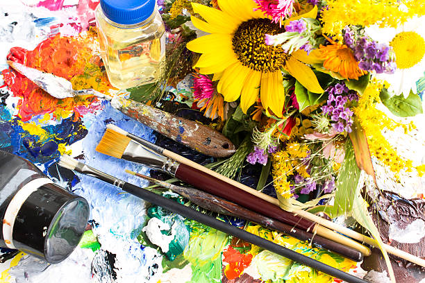 Palette with Painting Material and a Bouquet of Summer Flowers stock photo