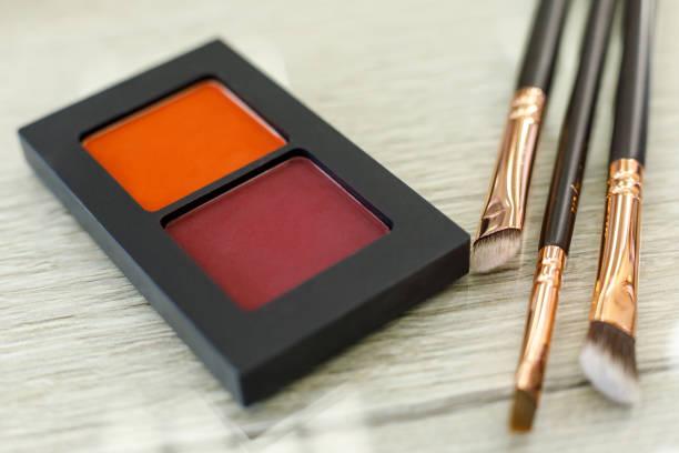 Palette mit Schatten und Pinsel auf dem Tisch im Schönheitssalon – Foto