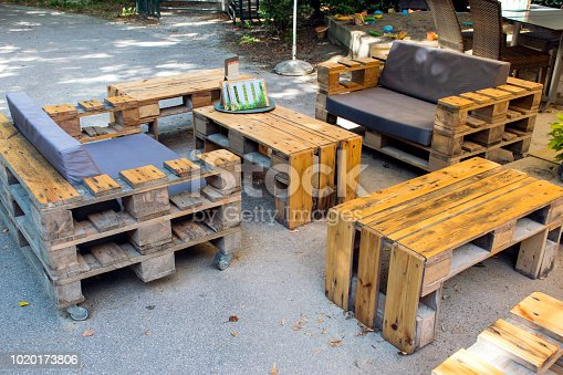 Wooden bench made of pallets for sitting with tables