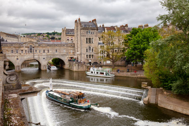 Palladian Pulteney Bridge and the weir at Bath Somerset South West England UK BATH, UK - JUN 12, 2013: City scene with weir on the River Avon near Palladian Pulteney Bridge bath england stock pictures, royalty-free photos & images