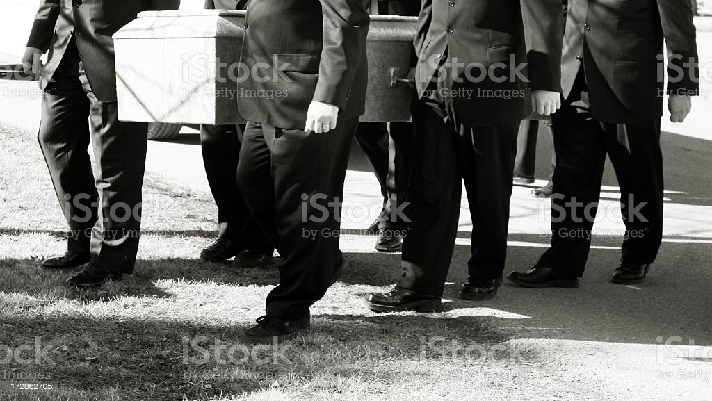 Pallbearers carry coffin to cemetery plot stock photo
