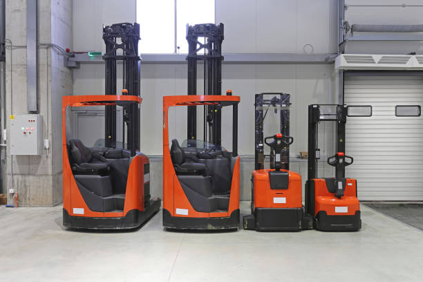 Pallet Trucks and Forklifts Pallet Trucks and Forklifts in Distribution Warehouse pallet jack stock pictures, royalty-free photos & images
