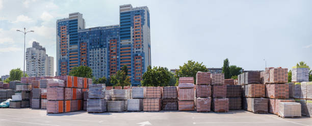 Pallets of different bricks on outdoor warehouse against of buildings stock photo