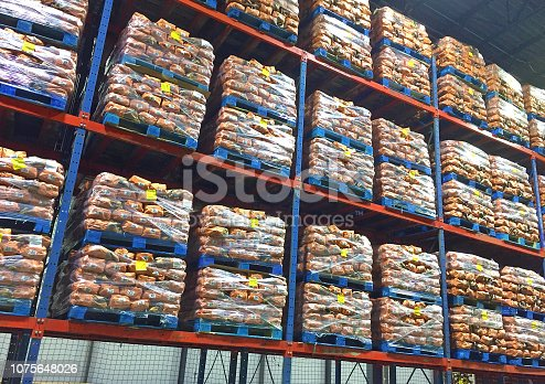 Pallets of 10 pound potato sacks stacked in distribution center.