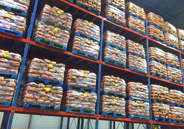 pallets of potato sacks stacked in distribution center. - pallet foto e immagini stock