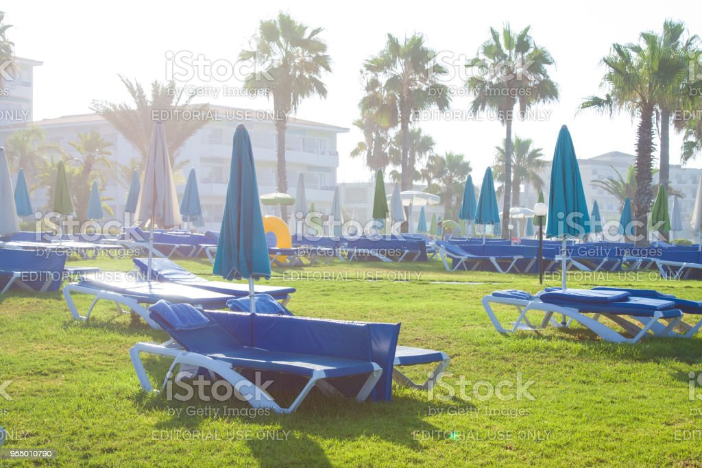 Palm beach with empty sunbeds against Constantinou Bros Athena Beach Hotel. The hotel was fully refurbished in the winter of 10/11 stock photo