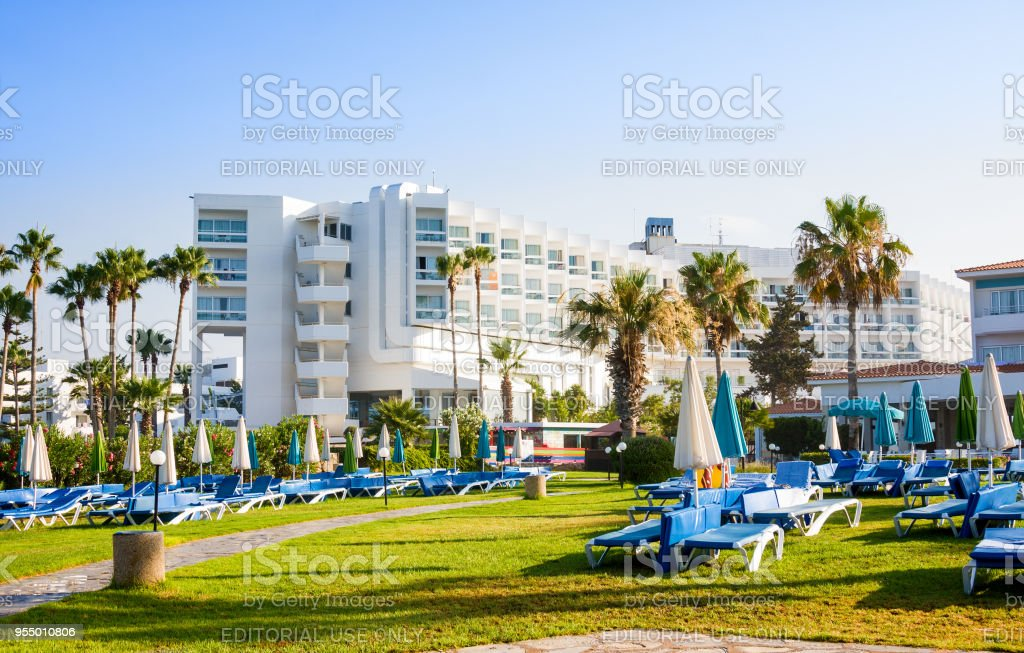 Palm beach with empty sunbeds against Constantinou Bros Athena Beach Hotel stock photo