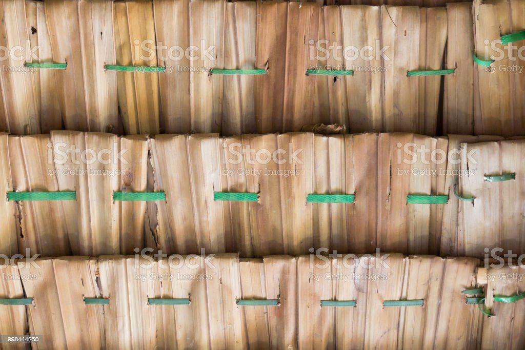 palm frond roof, made from the foliage branches of the palm tree. hand made rooftop traditional roof shingles in south of Asia stock photo