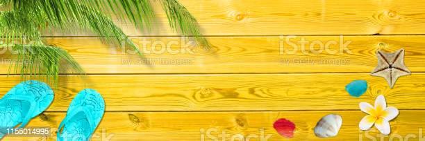 Palm leaf flip flops and seashells on yellow wooden planks panoramic picture id1155014995?b=1&k=6&m=1155014995&s=612x612&h=nb4wc2k87ru5tg4 dxda0lkkdyg0ficqoll0nywyo k=