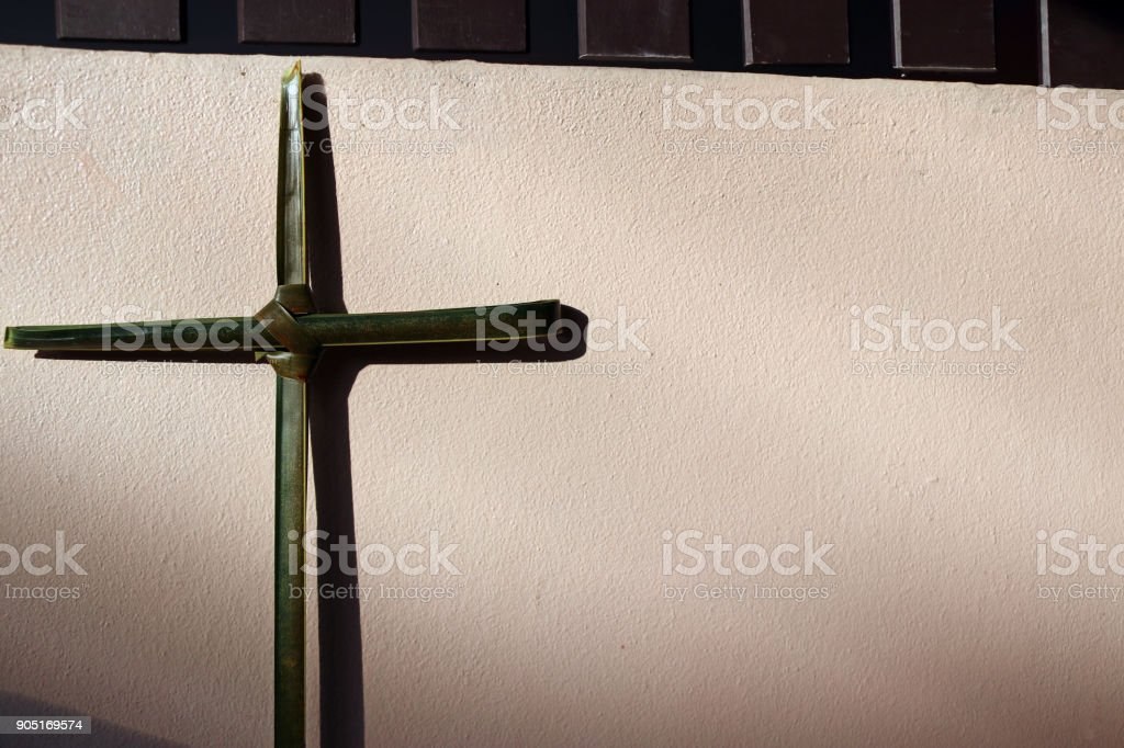 Palm leaf set cross to crucifix on the wall with the sunshine and shadow. stock photo