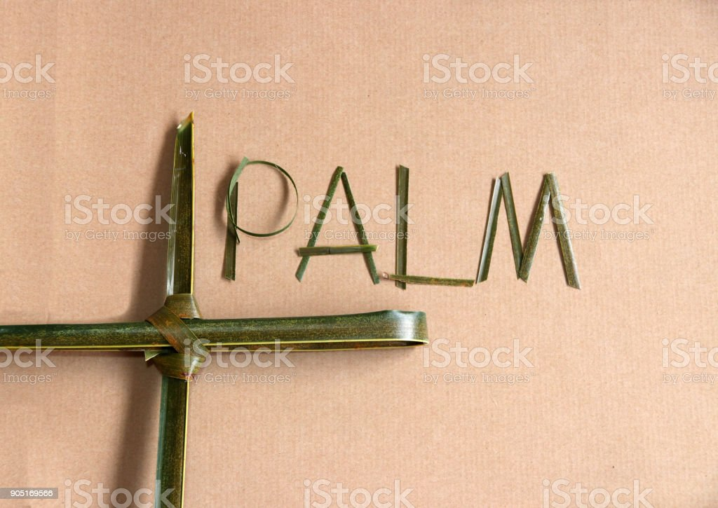 Palm leaf set cross to crucifix with palm leaf set to the word 'palm' on the brown paper background. stock photo