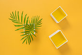 Palm tree leaves and decorative boxes on bright yellow background. Summer decor.