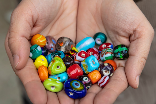 Palm of Hand Displaying Outstanding Original Handmade Glass Beads in Miscellaneous Varied Colors.