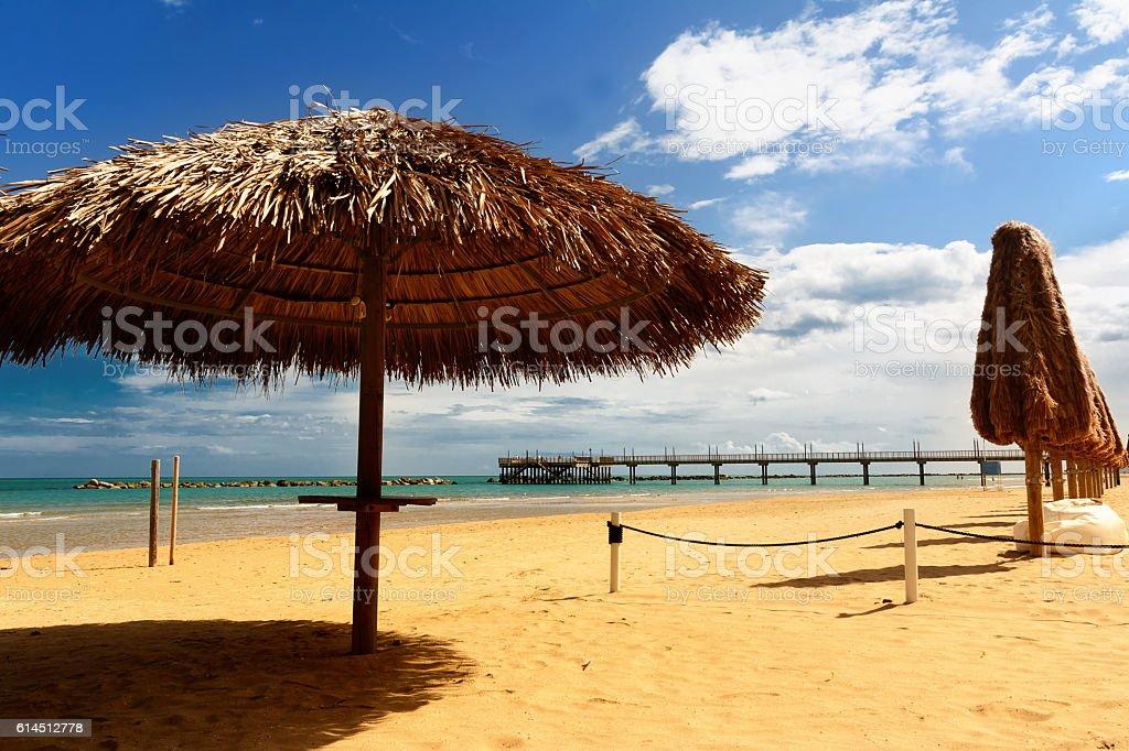 Palm parasol on the beach and pier in background i – zdjęcie