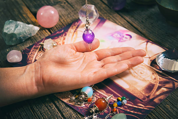 palm reading with pendulum - pendulum stock photos and pictures
