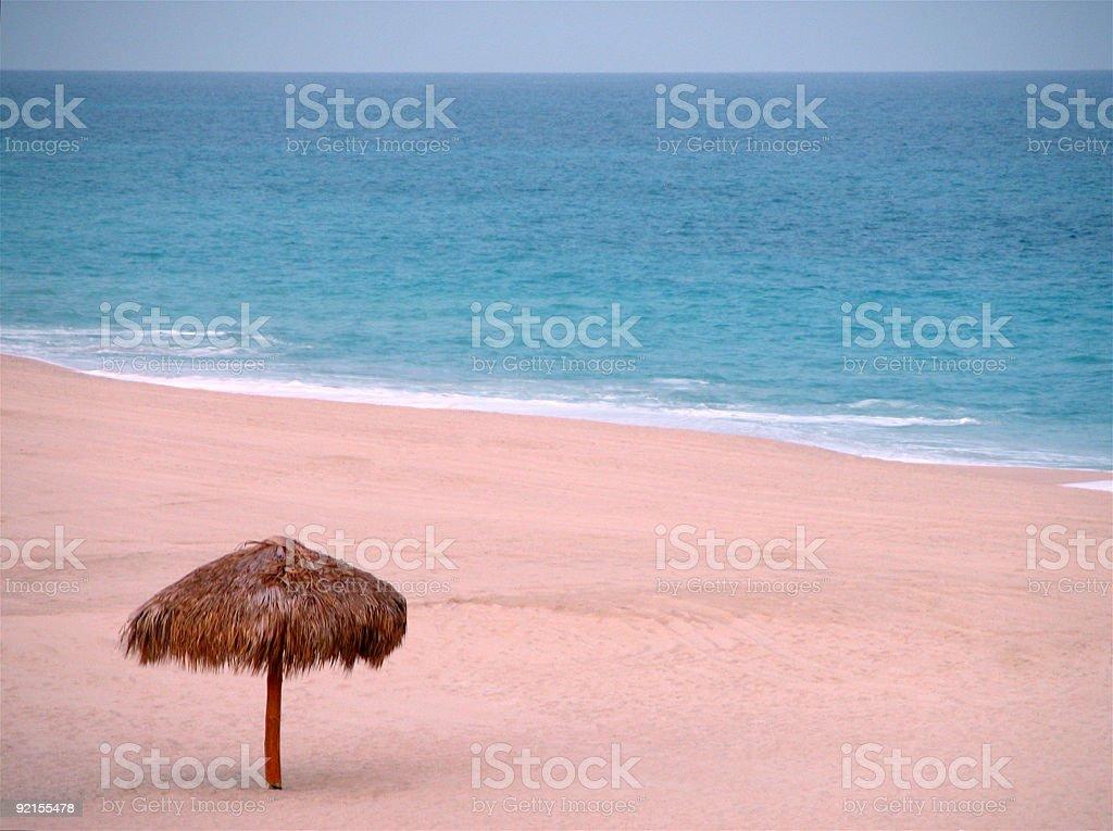Palm roofed umbrella on beach stock photo