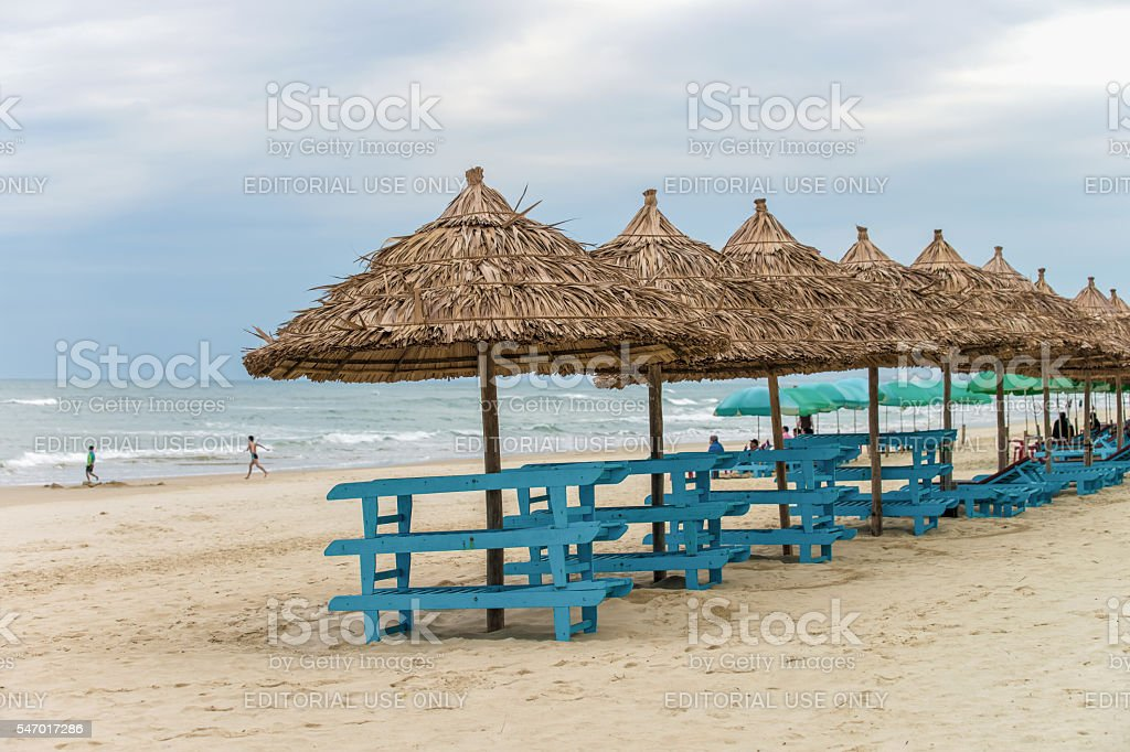 Palm shelters and tourists in China Beach in Da Nang stock photo