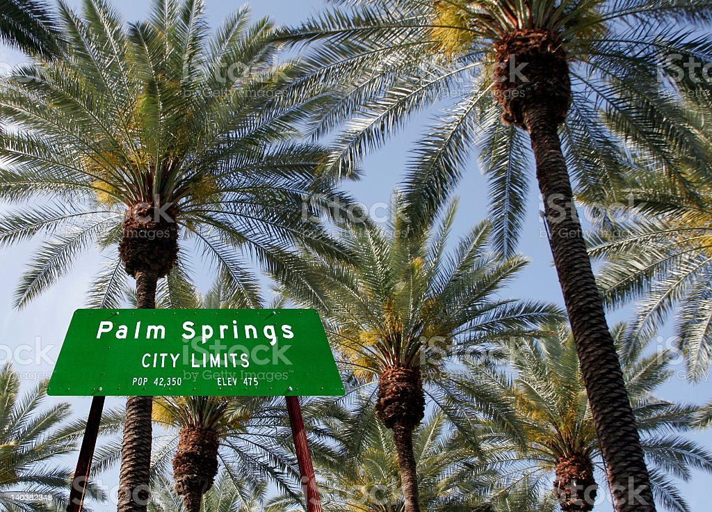 Palm Springs city limits sign in front of palm trees  stock photo