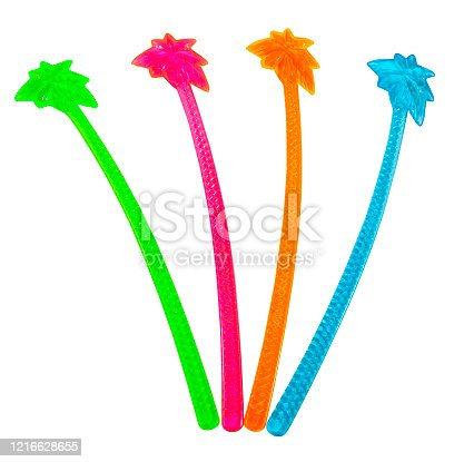 Isolated red, green, orange and blue plastic palm tree cocktail stirrers.