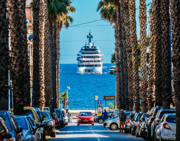 Palm tree lined boulevard leading to luxury yacht on ocean stock photo