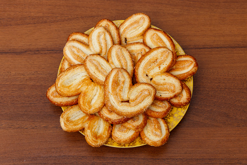 Palmier biscuits - french cookies made of puff pastry (also called palm leaves, elephant ears or french hearts) in a plate on wooden table