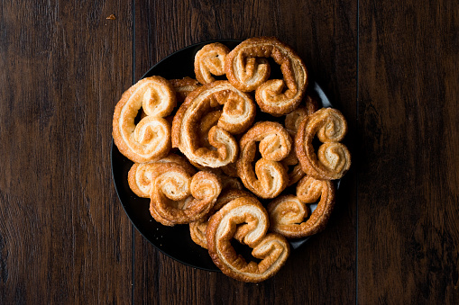 Palmier Cookies in Black Plate on Wooden Surface.