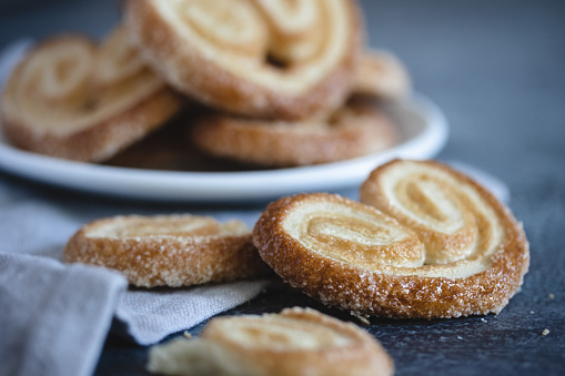 Palmier Puff Pastry. Delicious french palmier cookies with sugar on a white plate on dark background.