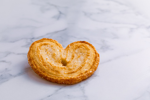 Palmier puff pastry on white marble background