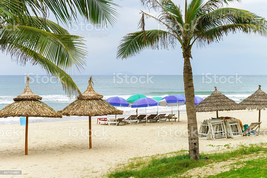 Palms and sunbeds in China Beach in Danang stock photo