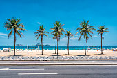 Palms on Ipanema Beach with blue sky, Rio de Janeiro, Brazil. Famous mosaic boardwalk in front of palms