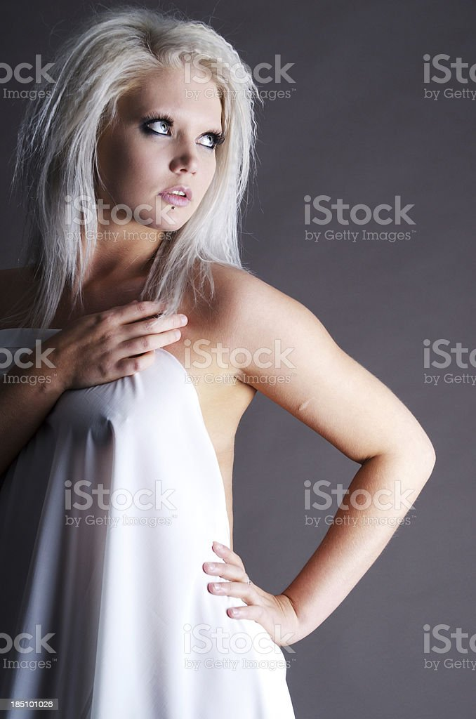 Paltinum blonde in white sheet on grey stock photo