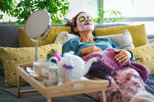 Pampering myself on weekends. Young woman with a mask and rolls of cucumber on her face is enjoying a morning weekend. beauty treatment stock pictures, royalty-free photos & images