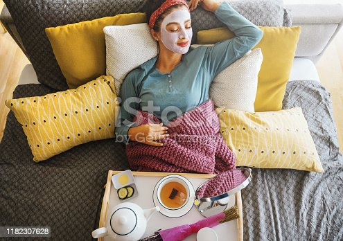 Young woman with a mask on her face is enjoying a morning weekend.