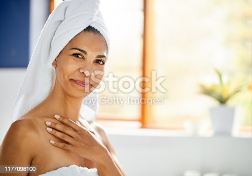 Portrait of a young woman wearing in towel applying moisturizer on her body