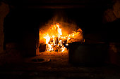 Pan and a fire in the village stove. Russia.