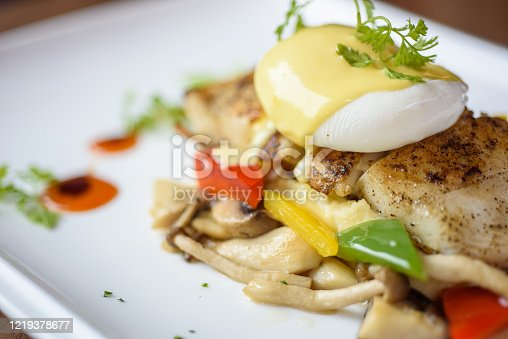 Pan fried dory fish topped with egg Benedict and heart shape dressing
