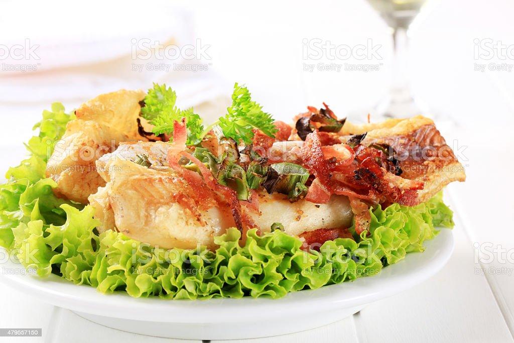 Filés de peixe fritos com pedacinhos crocantes de bacon - foto de acervo