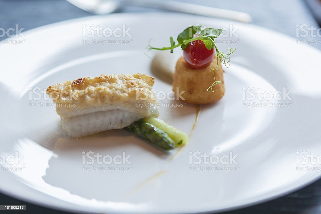 Pan fried snapper with a parmesan crust and baby vegetables stock photo